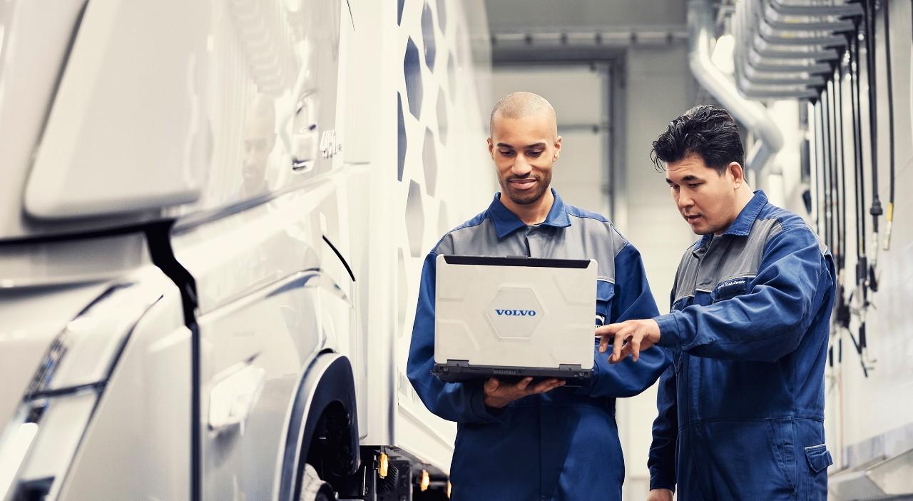 Dva servisní technici Volvo stojí unákladního vozidla asledují notebook