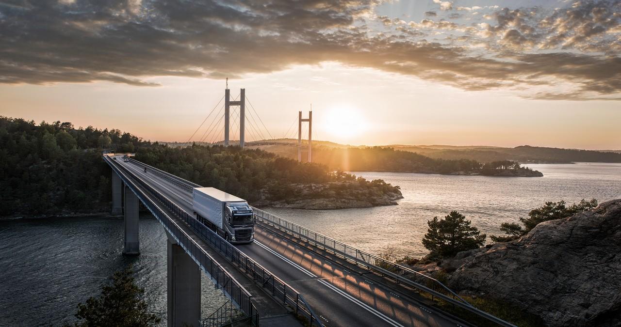 Nákladní vozidlo Volvo přejíždí most přes vodu při západu slunce