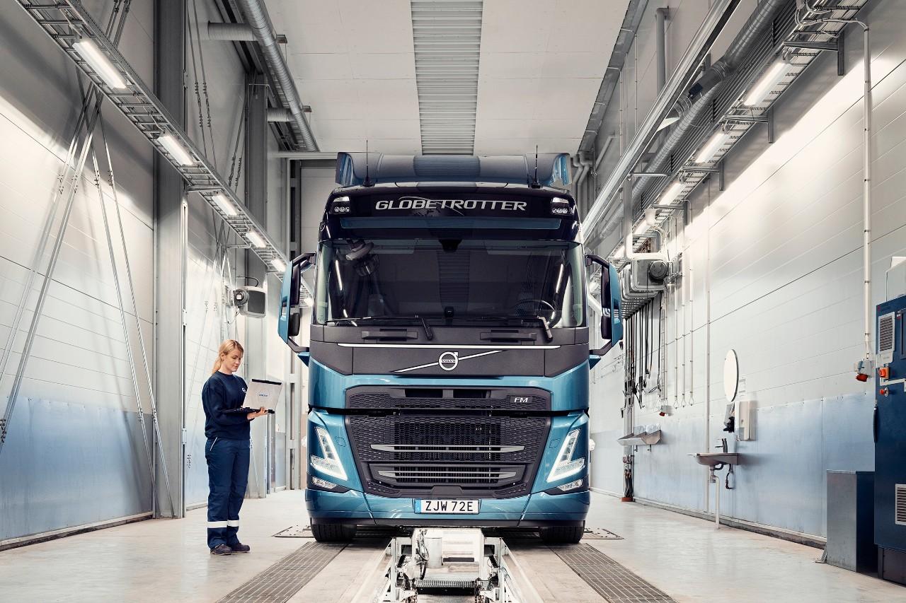Servisní technik Volvo drží počítač astojí unákladního vozidla