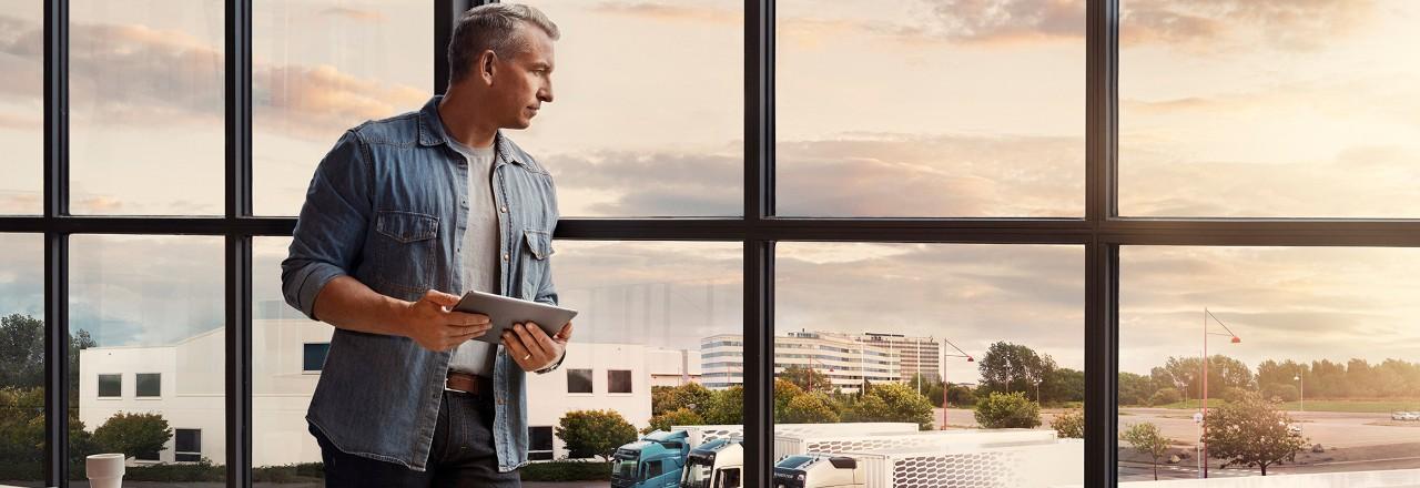 Muž držící tablet stojí u okna a dívá se dolů na svůj vozový park